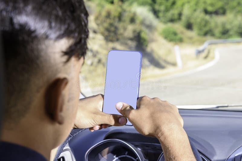 Giovane autista, facendo uso dello smartphone, sulla strada nell'automobile immagini stock