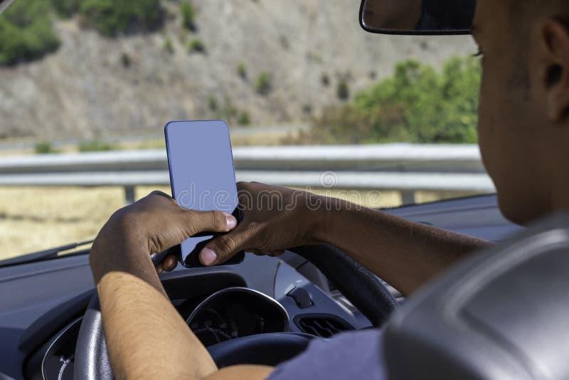 Giovane autista, facendo uso dello smartphone, sulla strada nell'automobile immagine stock libera da diritti