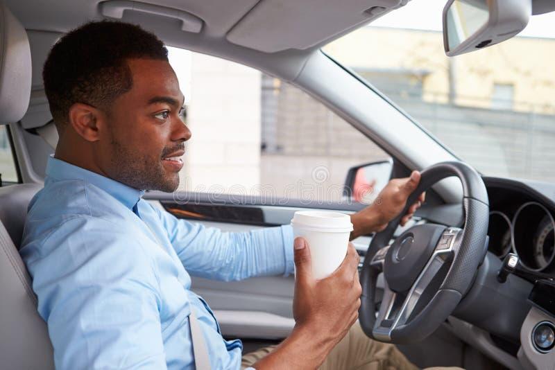 Giovane autista maschio afroamericano con caffè, nella vista dell'automobile immagini stock