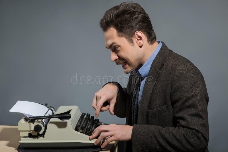 Giovane autore felice che scrive alla macchina da scrivere immagine stock