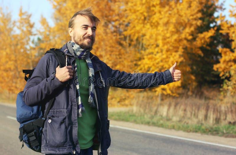 Giovane autostoppista barbuto dei pantaloni a vita bassa con la prova dello zaino all'automobile di fermo immagini stock libere da diritti