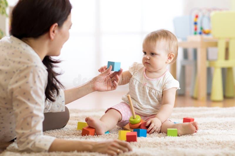 Giovane babysitter che gioca con poco bambino, all'interno immagini stock libere da diritti