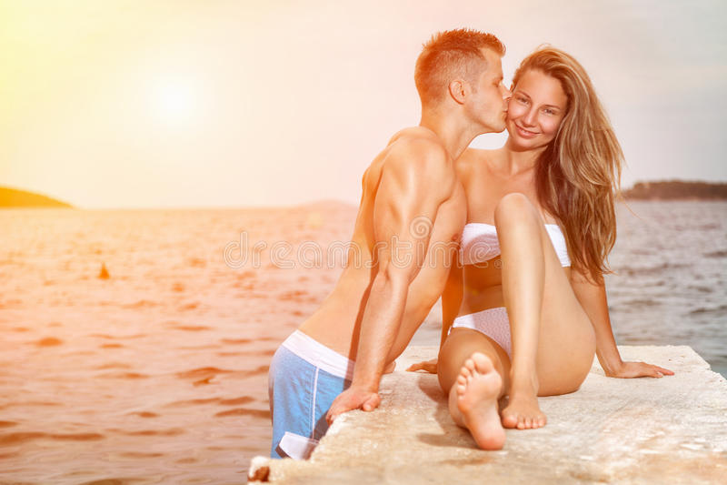 Giovane bacio felice delle coppie su una spiaggia durante il tramonto fotografia stock