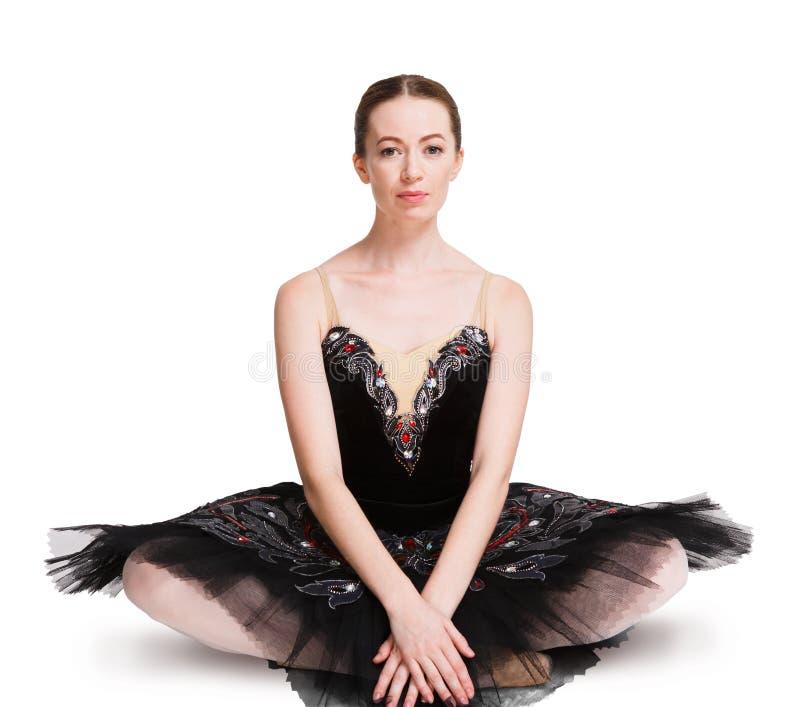 Giovane ballerina che si siede sul pavimento al fondo bianco fotografia stock libera da diritti