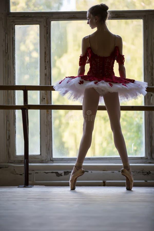 Giovane ballerina elegante che sta vicino ad una grande finestra in un ballo immagini stock libere da diritti