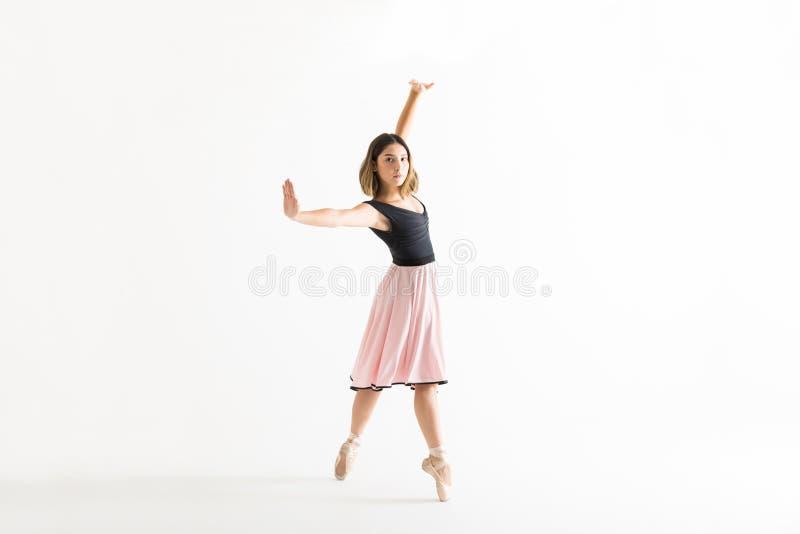 Giovane ballerina sicura che balla con garbo sul fondo bianco fotografia stock libera da diritti