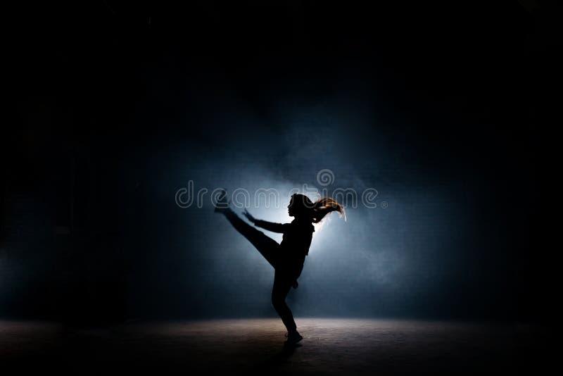 Giovane ballerino con alto da fare rizzare i capelli lungo la sua gamba sulla fase scura fotografia stock libera da diritti