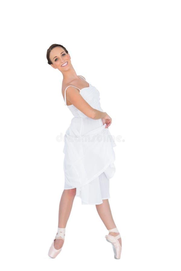 Giovane ballerino di balletto sorridente che sta sulle sue punte dei piedi immagini stock