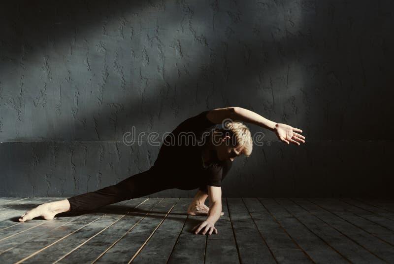 Giovane ballerino di talento che mostra la sua flessibilità nello studio fotografie stock libere da diritti