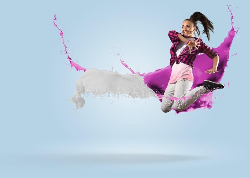 Giovane ballerino femminile che salta con la spruzzata di pittura fotografia stock libera da diritti