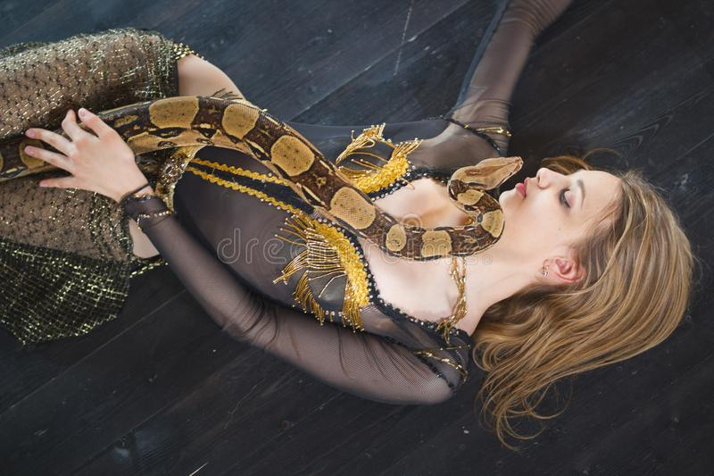 Giovane ballerino femminile che si trova sul pavimento con un serpente sul suo corpo fotografia stock libera da diritti