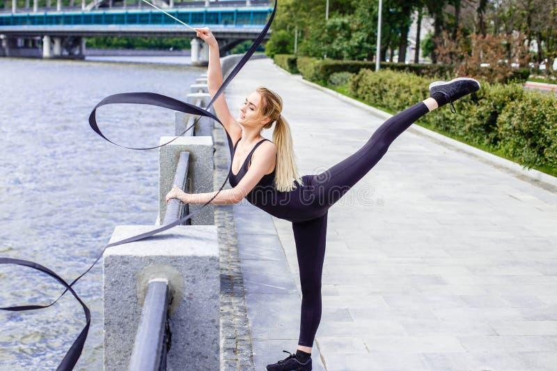 Giovane ballo professionale della donna della ginnasta con il nastro sul lungomare immagini stock libere da diritti