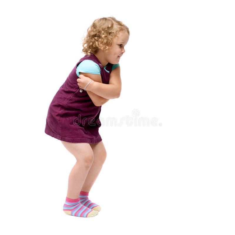 Giovane bambina che salta sopra il fondo bianco isolato immagini stock