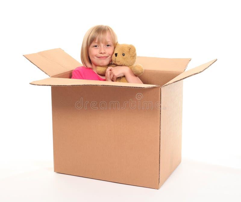 Giovane bambina che si siede all'interno della casella fotografia stock