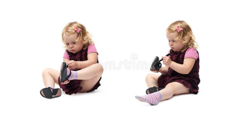 Giovane bambina che si siede sopra il fondo bianco isolato fotografie stock libere da diritti