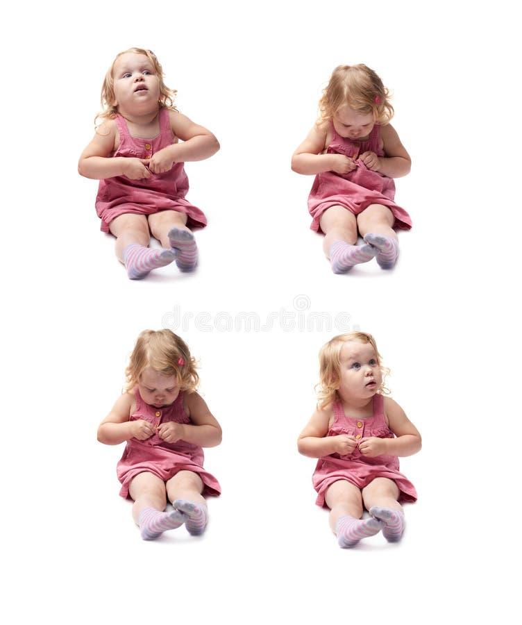 Giovane bambina che si siede sopra il fondo bianco isolato fotografia stock