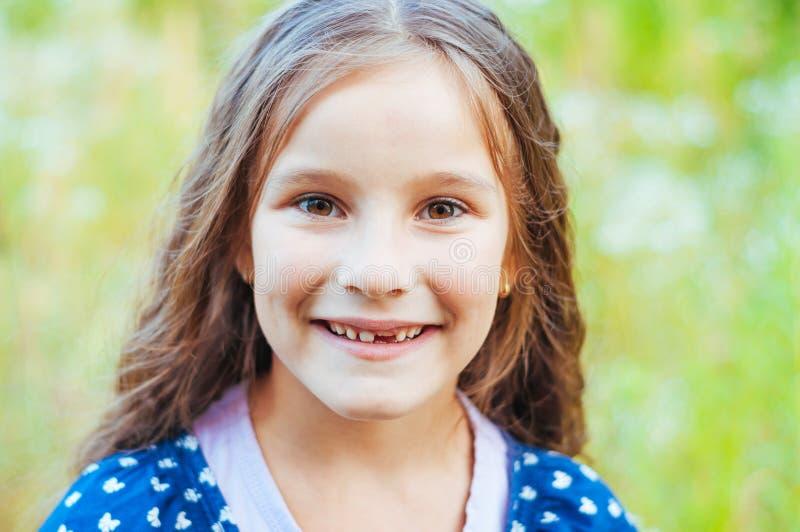 Giovane bambina con capelli lunghi senza sorrisi del dente anteriore, luce naturale immagini stock