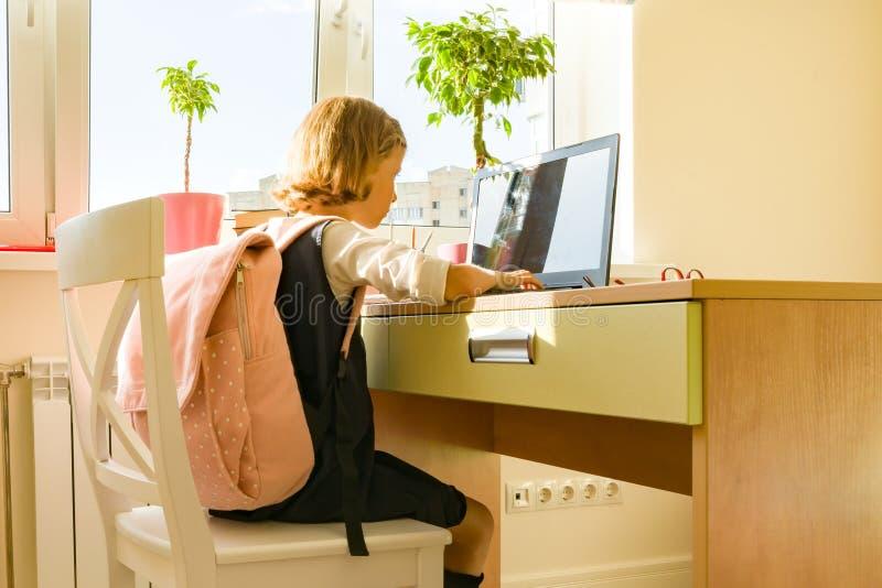 Giovane bambina in vetri con uno zaino della scuola che funziona al computer, computer portatile del pirata informatico immagini stock