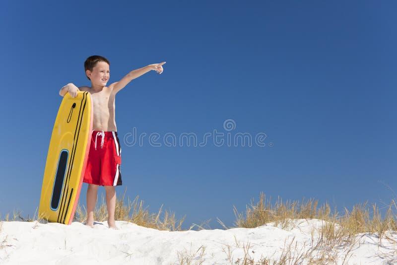 Giovane bambino del ragazzo su una spiaggia con indicare del surf immagini stock libere da diritti