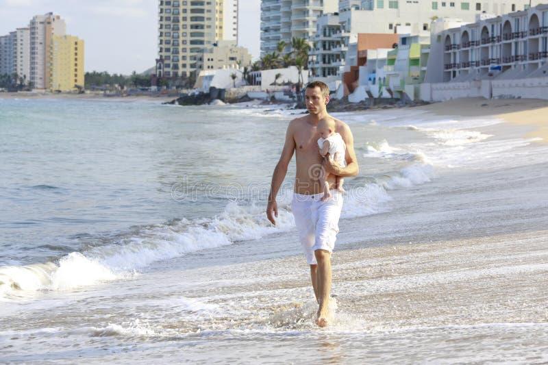 Giovane bambino della tenuta del padre sulla spiaggia vicino all'oceano con lighthous immagine stock libera da diritti