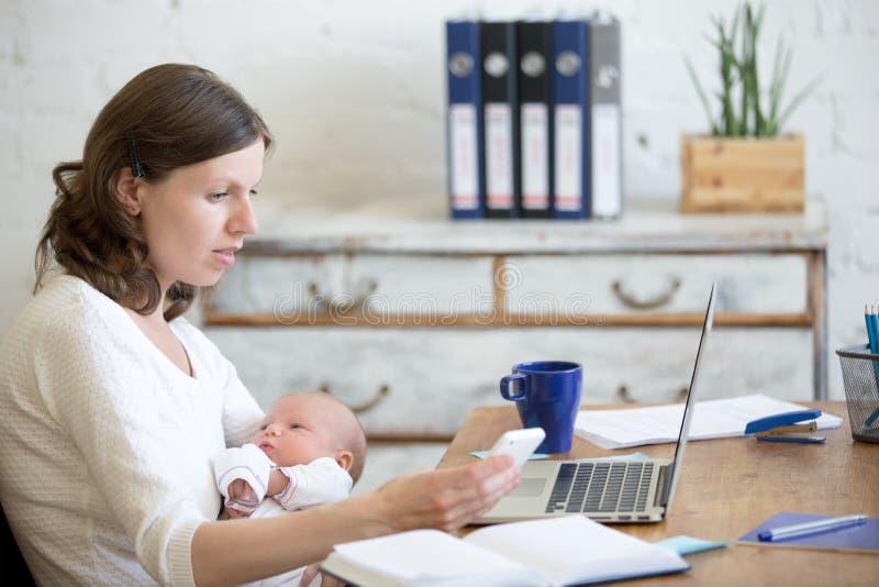 Giovane bambino di funzionamento e della tenuta della mamma nell'ufficio fotografie stock