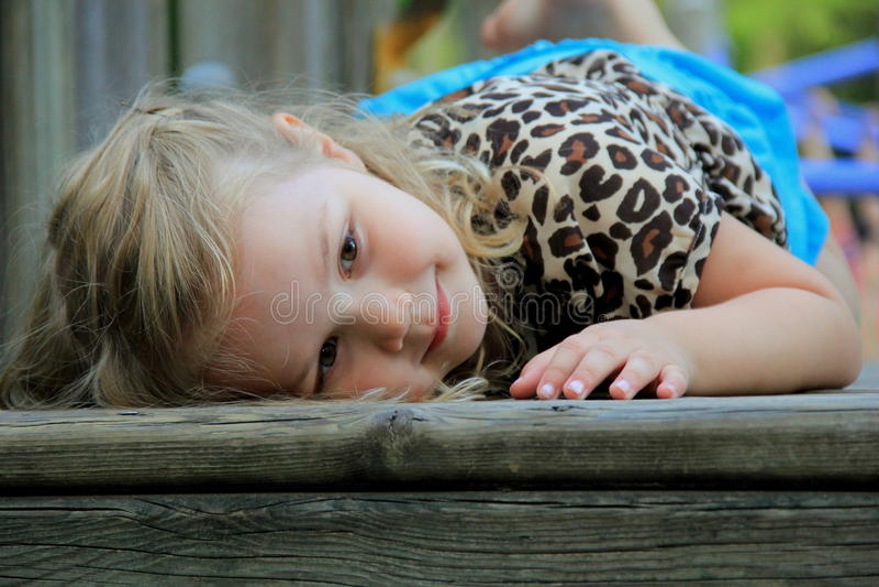Giovane bambino sorridente che si riposa al campo da giuoco immagine stock libera da diritti