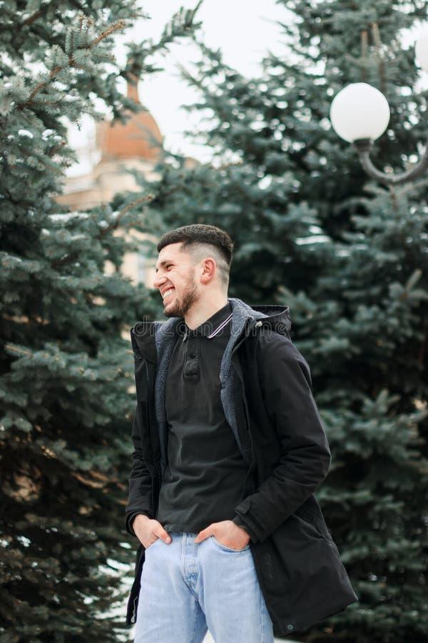 Giovane barbuto bello all'aperto in cappotto del nero di inverno fotografia stock libera da diritti