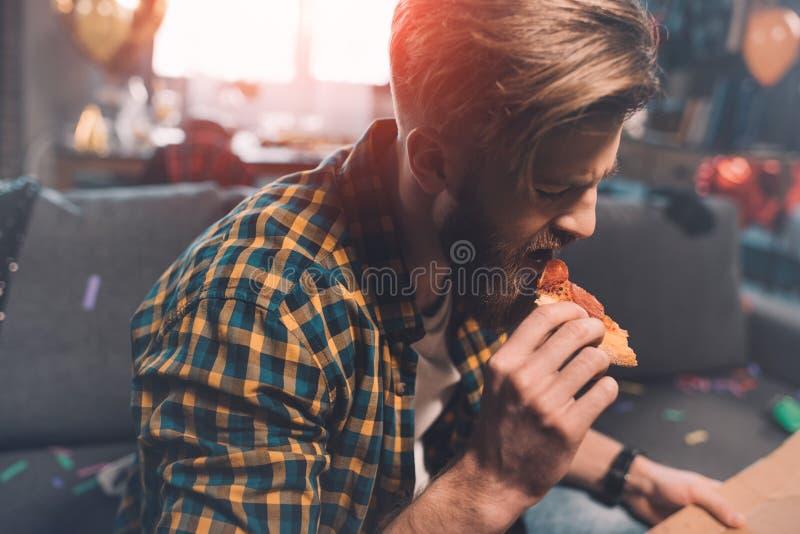 Giovane barbuto con postumi di una sbornia che mangia pizza dopo il partito fotografia stock