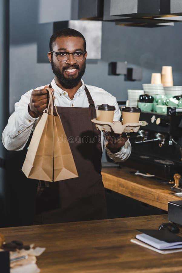 giovane barista afroamericano sorridente bello che tiene le tazze di caffè ed i sacchi di carta eliminabili in caffè fotografie stock