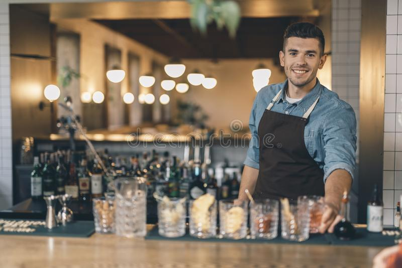 Giovane barista amichevole davanti ai cocktail sul contatore della barra immagine stock