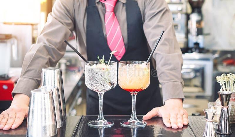 Giovane barista che fa i cocktail alle bevande serventi del barista contro- della barra - lavoro, passione e concetto del mixolog fotografia stock
