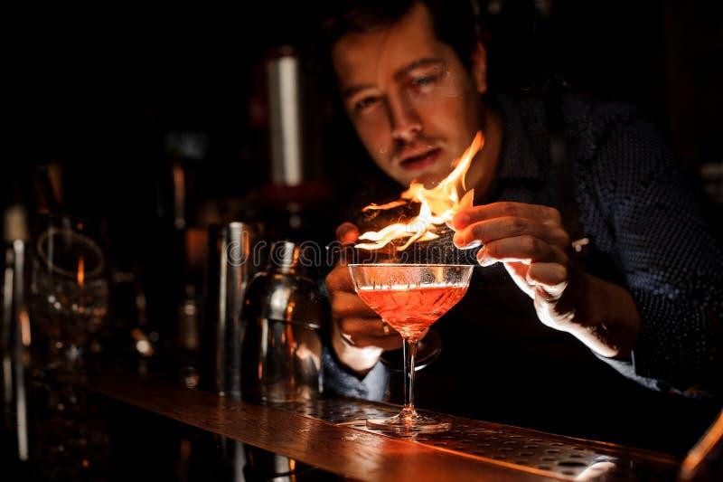Giovane barista che fa un cocktail fresco con una nota fumosa fotografia stock