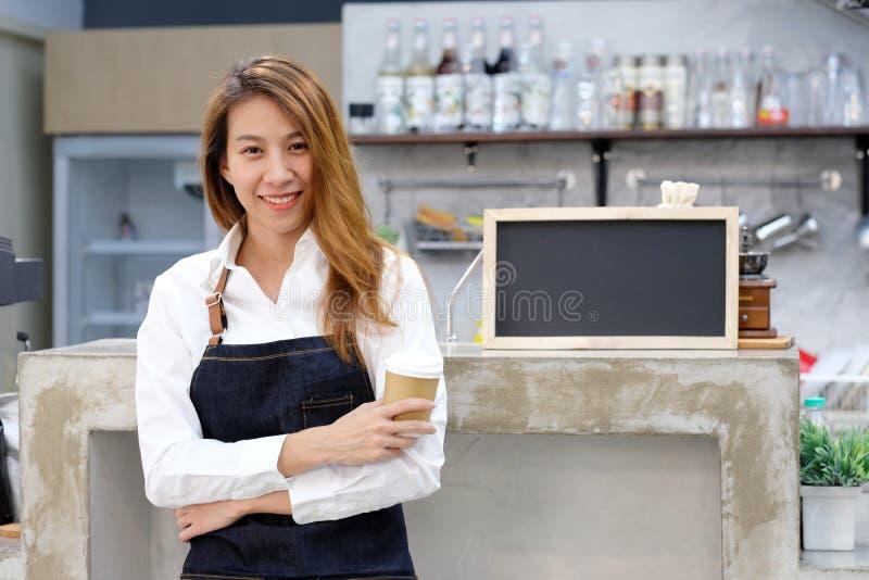 Giovane barista della donna dell'Asia che tiene una tazza di caffè diaposable con MP immagine stock