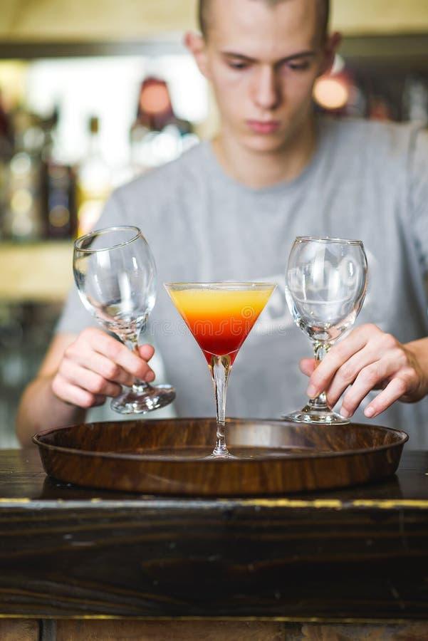 Giovane barista o un cameriere che fa un cocktail fotografia stock libera da diritti
