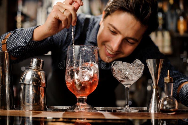 Giovane barista sorridente che mescola cocktail alcolico fresco con gli sciroppi immagini stock