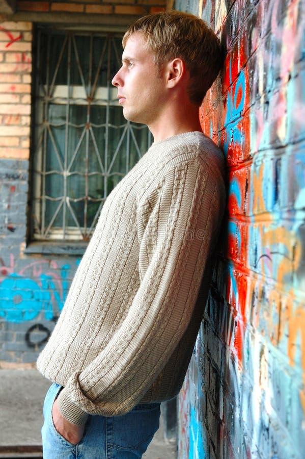 Giovane basamento alla moda dell'uomo vicino al muro di mattoni dei graffiti. fotografia stock