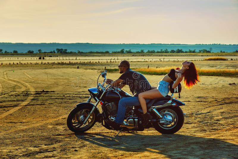Giovane bei donna ed uomo che si siedono su un motociclo immagini stock libere da diritti