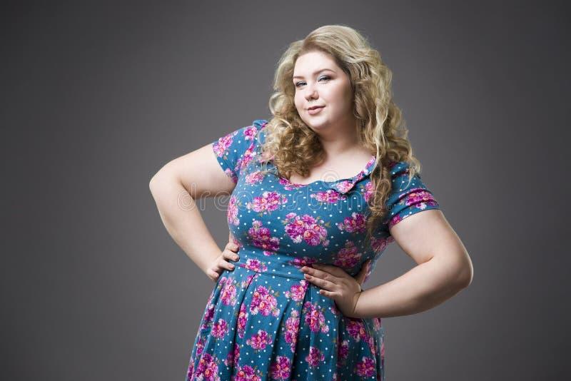 Giovane bella bionda felice più il modello nei dres, ritratto di dimensione della donna del xxl sul fondo grigio dello studio immagine stock libera da diritti