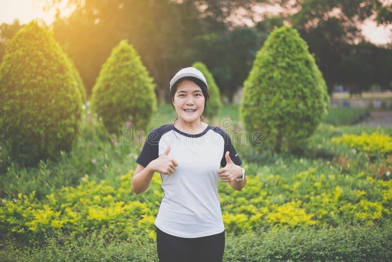 Giovane bella condizione asiatica felice e sorridente e pollice della donna sulle mani mentre prendendo una rottura dopo il funzi immagini stock
