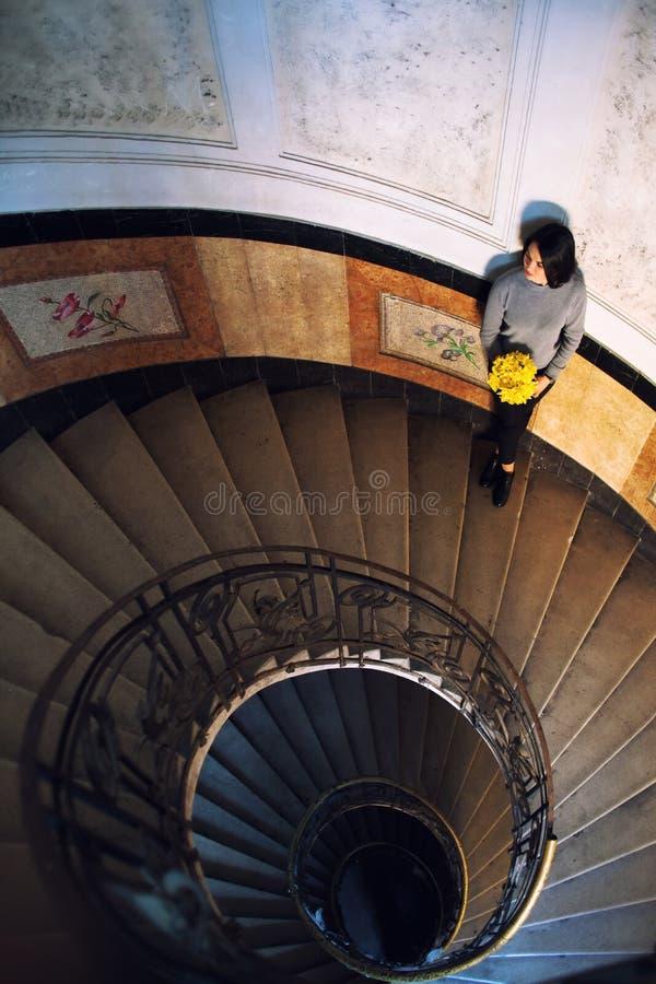 Giovane bella condizione della donna sulla vecchia scala a chiocciola rotonda Vista superiore fotografie stock libere da diritti