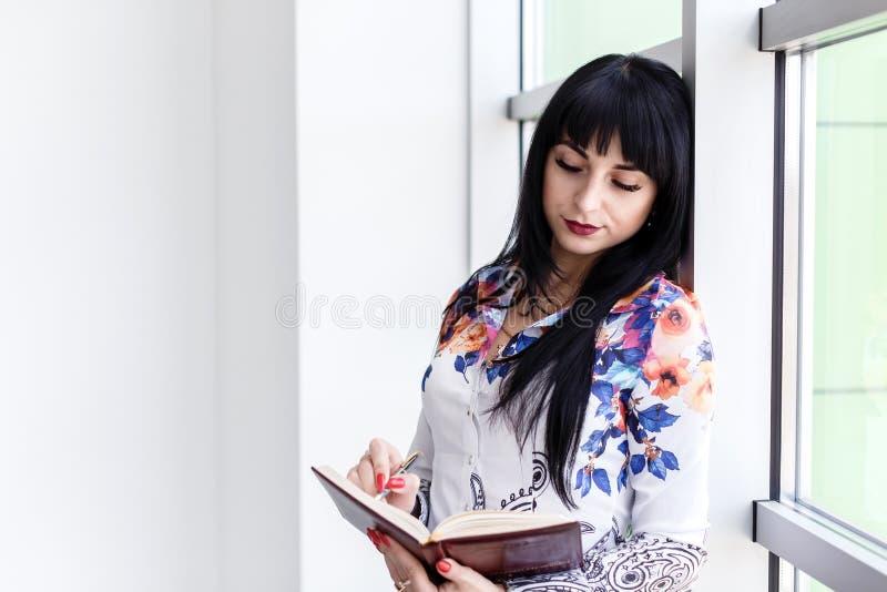 Giovane bella condizione seria della donna vicino alla finestra, scrivendo in un taccuino, guardante al taccuino fotografie stock