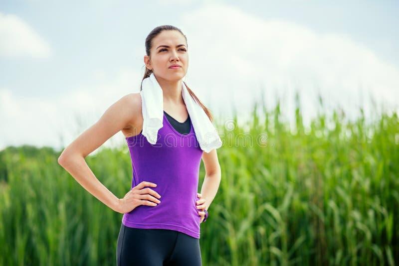 Giovane bella condizione sportiva della donna prima o dopo l'allenamento ed il funzionamento Messo a fuoco sugli esercizi, sul fo fotografia stock