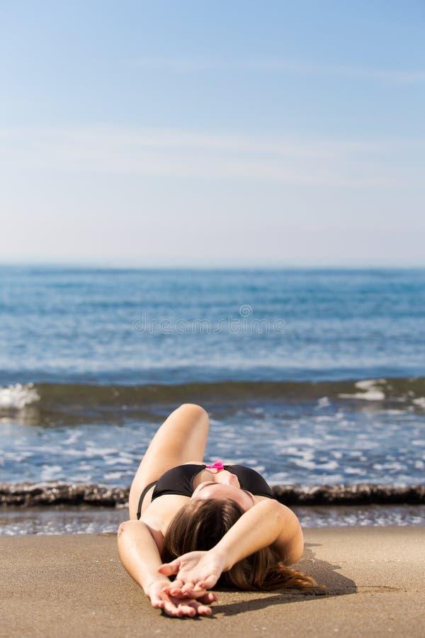 Giovane bella donna abbronzata che mette sulla spiaggia del mare fotografia stock libera da diritti