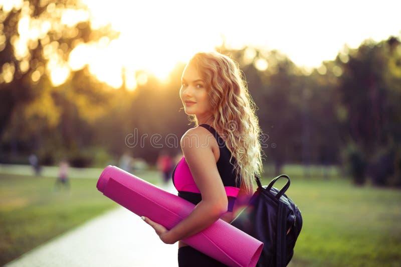 Giovane bella donna in abiti sportivi Lei ` s che tiene una stuoia di addestramento Andando fare gli sport che si preparano, ginn immagini stock libere da diritti
