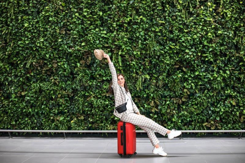 Giovane bella donna in aeroporto contro la parete verde fotografia stock libera da diritti