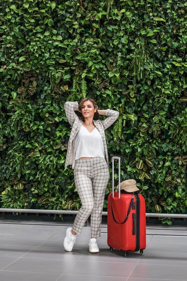 Giovane bella donna in aeroporto contro la parete verde immagini stock libere da diritti