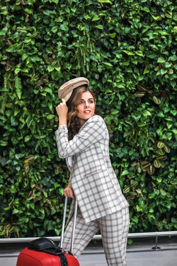 Giovane bella donna in aeroporto contro la parete verde fotografie stock