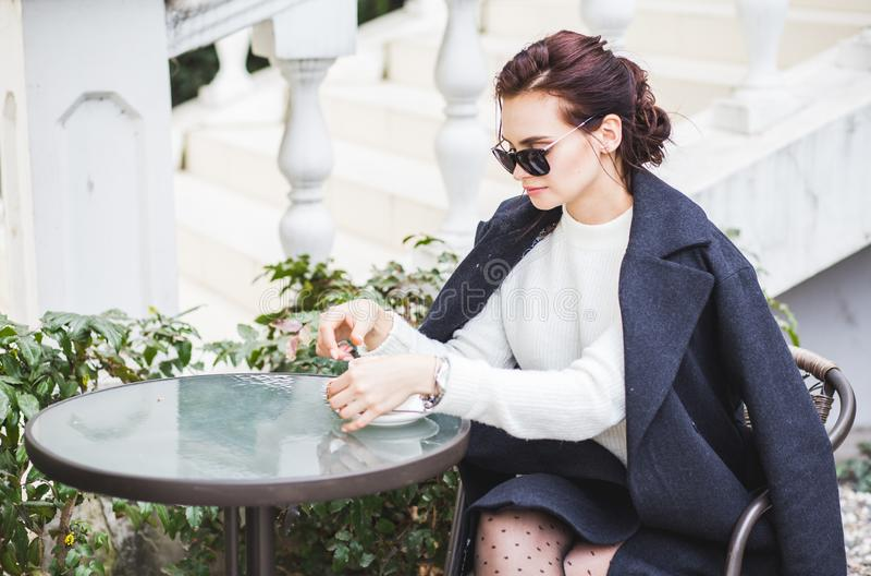 Giovane bella donna alla moda in occhiali da sole che si siedono in un caffè bevente all'aperto del caffè fotografie stock libere da diritti