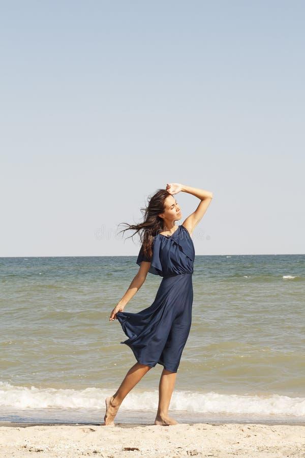 Giovane bella donna alla spiaggia in vestito blu immagine stock