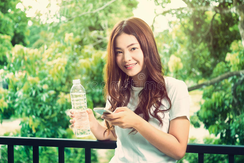 Giovane bella donna asiatica in buona salute felice che tiene chiara bottiglia o fotografia stock